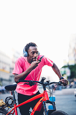 Young man with e bike and headphones using smartphone in the city - p300m2121664 von Oscar Carrascosa Martinez