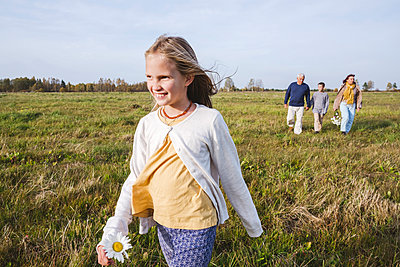 Smiling girl walking on field while family in background - p300m2225949 by Ekaterina Yakunina