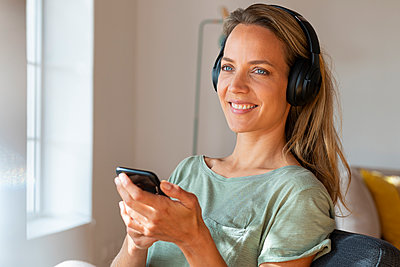 Smiling woman with headphones holding smart phone at home - p300m2276389 by Steve Brookland