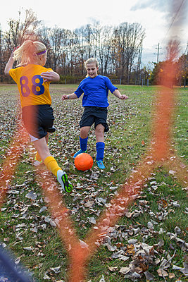 Caucasian girls playing soccer in field - p555m1305764 by Eric Raptosh Photography