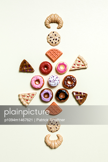 Directly above shot of various dessert toys on white background - p1094m1467621 by Patrick Strattner