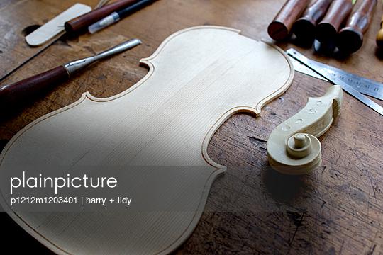 Neuer Geigenboden und Geigenschnecke auf einer alten Werkbank - p1212m1203401 von harry + lidy