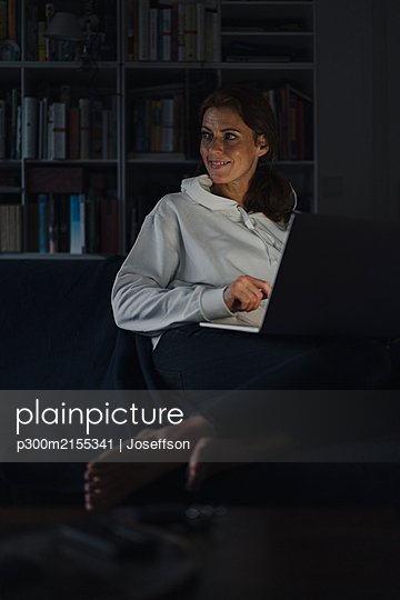 Woman sitting on couch of dark living room, using laptop - p300m2155341 by Joseffson