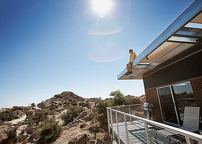 A man sitting on the roof overhang of an eco home in the desert landscape. - p1100m1107167 by Mint Images