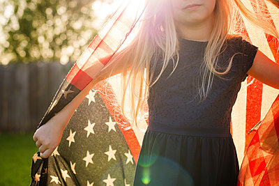 Midsection of girl with American flag in backyard - p1166m1182549 by Cavan Images