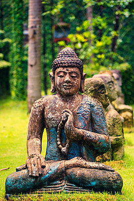 Close-up of Buddha statue on grassy field - p1166m1575936 by Cavan Social
