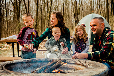 Smiling family roasting marshmallows over campfire in woods during Fal - p1166m2129766 by Cavan Images