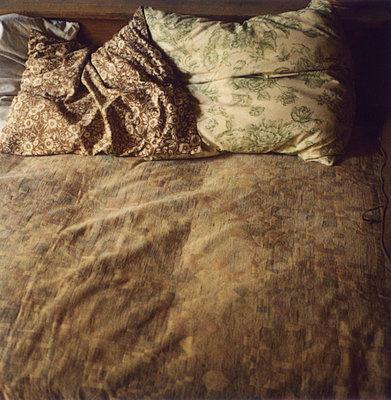 Gemusterte Kopfkissen auf einem Bett - p1270m1114443 von Nathalie Baetens