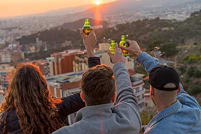 Spain, Barcelona, three friends with beer bottles on a hill overlooking the city at sunset - p300m1562582 by VITTA GALLERY