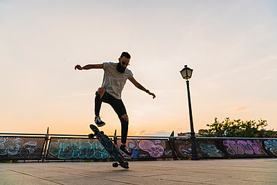 Young man doing a skateboard trick in the city at sunset - p300m2060990 by Kike Arnaiz