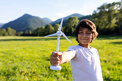 Smiling boy holding wind turbine toy while standing in meadow - p300m2221320 by Valentina Barreto