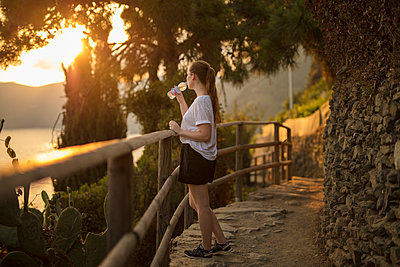 Teenage girl drinking water and looking at view - p312m2079784 by Depiction AB