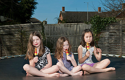 Girls eating popsicles on trampoline - p429m659559f by Henn Photography