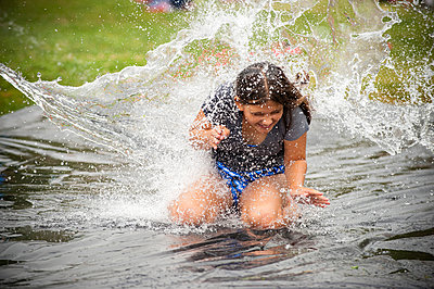 Water splashing on girl on outdoor plastic tarp - p555m1303530 by Stephen Simpson Inc