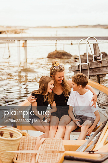 Happy family sitting in boat during summer vacation - p426m2238307 by Maskot