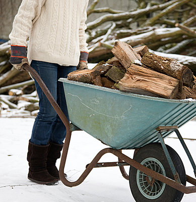 Woman walking through the snow with a wheelbarrow full of wood logs - p1231m1043135 by Iris Loonen