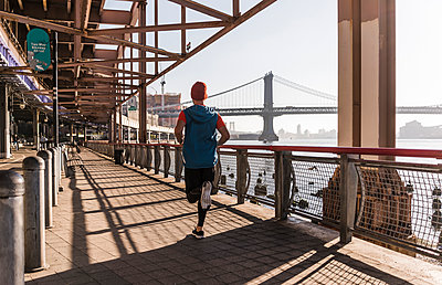 USA, New York City, man running at East River - p300m1192078 by Uwe Umstätter