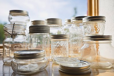 Assortment of empty canning jars on table - p328m906626f by Hero Images