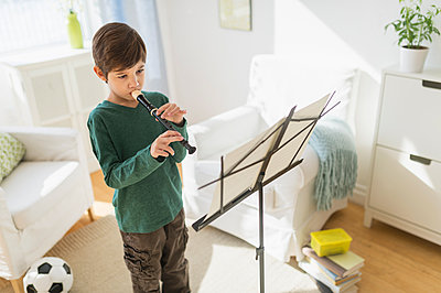 Hispanic boy practicing recorder in living room - p555m1419271 by JGI/Tom Grill