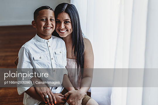 Portrait of young mother and school-aged boy sitting and smiling - p1166m2130961 by Cavan Images