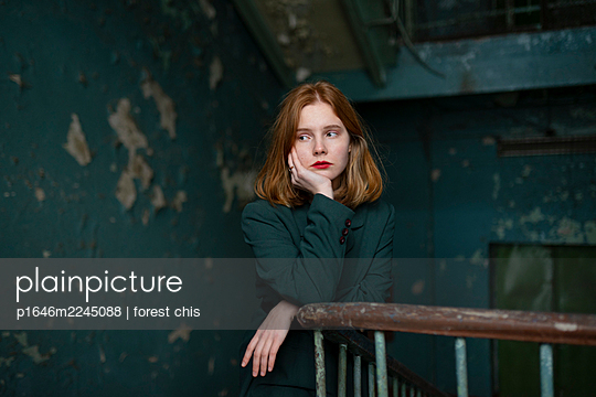 Sad teenage girl with red hair in the staircase - p1646m2245088 by Slava Chistyakov