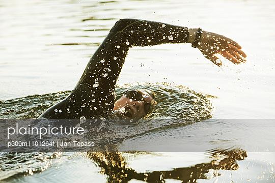 Triathlete swimming in lake - p300m1101264f by Jan Tepass