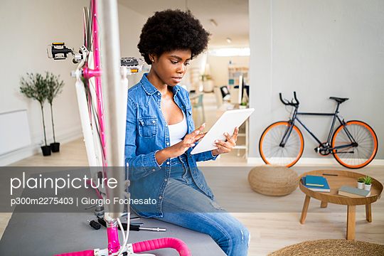 Afro woman watching tutorial on digital tablet while repairing bicycle at home - p300m2275403 by Giorgio Fochesato