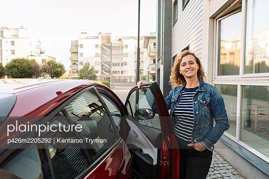 Portrait of smiling woman standing by car - p426m2205292 by Kentaroo Tryman