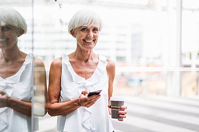 Portrait of smiling senior woman with cell phone and takeway coffee outdoors - p300m2028828 by Daniel Ingold
