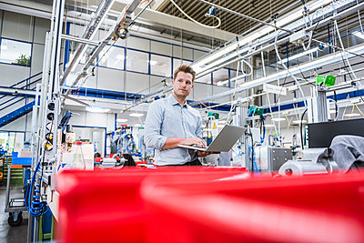 Man using laptop in factory - p300m2197863 by Daniel Ingold