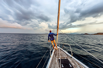 Man standing on bow of yacht, Lombok, Indonesia - p343m2010744 by Konstantin Trubavin
