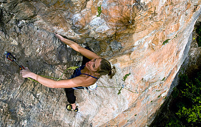 A climber makes her way up a steep and difficult route on the limestone cliffs in the Aveyron region, near Millau and Toulouse, south west France, Europe - p8713175 by David Pickford
