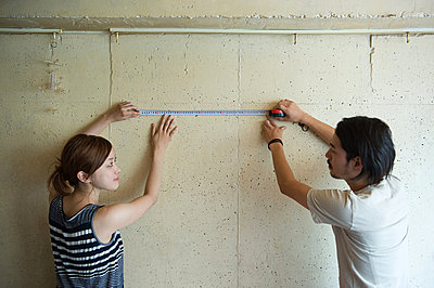 Young couple measuring wall - p9245912f by Image Source