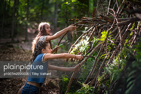 Two girls building a hut in the forest - p1007m2220006 by Tilby Vattard