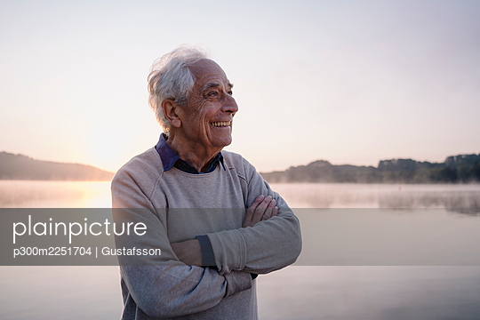 Smiling senior man looking away while standing with arms crossed against lake - p300m2251704 by Gustafsson
