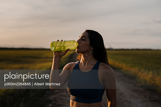 Woman drinking water through bottle against sky - p300m2264845 by Albert Martínez