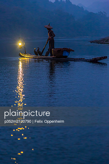 Man paddling on raft at dusk in Sichuan, China - p352m2120790 by Felix Oppenheim