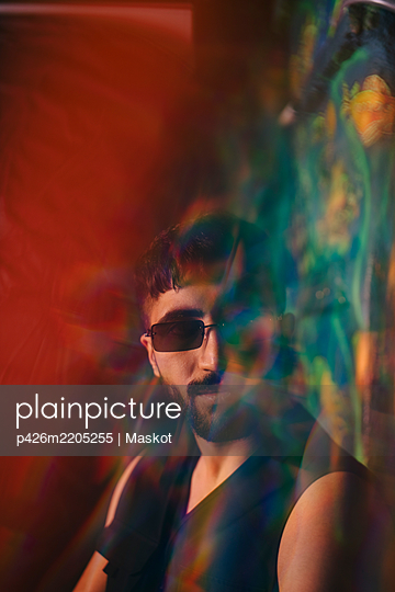 Portrait of young man wearing sunglasses at illuminated restaurant - p426m2205255 by Maskot