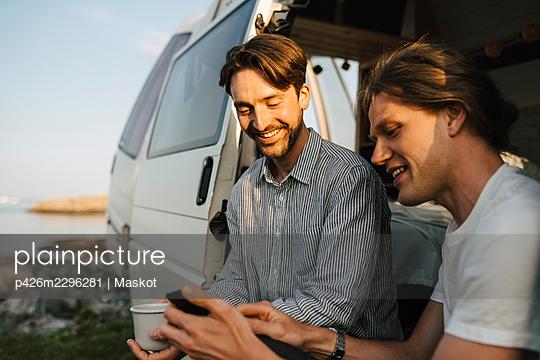 Man sharing smart phone with boyfriend - p426m2296281 by Maskot