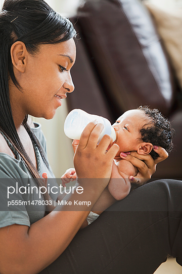 Mixed race mother feeding bottle to newborn baby - p555m1478033 by Mike Kemp