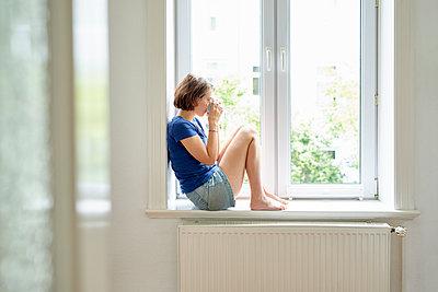 Frau sitzt auf der Fensterbank - p1124m1481050 von Willing-Holtz