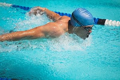Young Caucasian male swimmer swimming butterfly stroke in swimming pool - p1315m2091025 by Wavebreak
