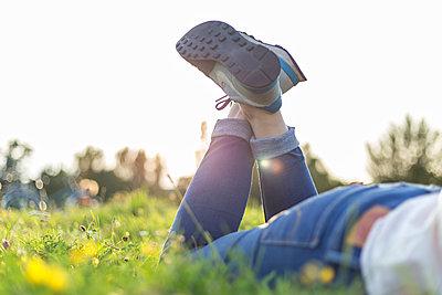 Junge Frau liegt entspannt im Park - p1396m1481205 von Hartmann + Beese