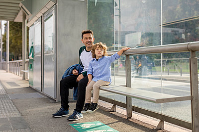 Father and son sitting at tram stop in the city - p300m2070418 von Mauro Grigollo