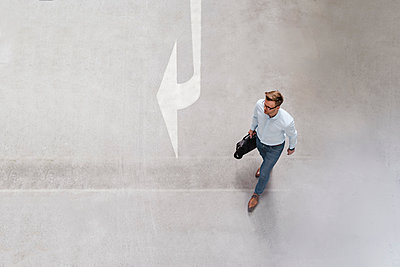 High angle view of businessman walking in city - p300m2206574 by Daniel Ingold