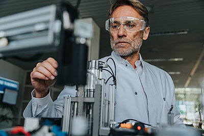 Male scientist with protective eyewear examining machine in laboratory - p300m2206969 by Mareen Fischinger