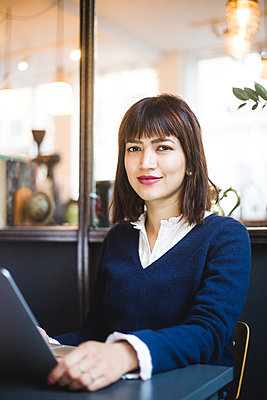 Portrait of confident female professional sitting with laptop at office - p426m2089042 by Maskot