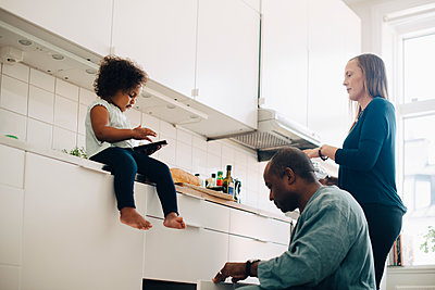 Girl using smart phone while mother and father working in kitchen at home - p426m2097919 by Maskot