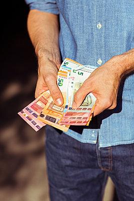 Mann hält einige Geldscheine in der Hand - p432m1586841 von mia takahara