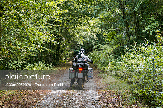 Father and son on a motorbike trip on a forest track - p300m2059920 by Francesco Buttitta
